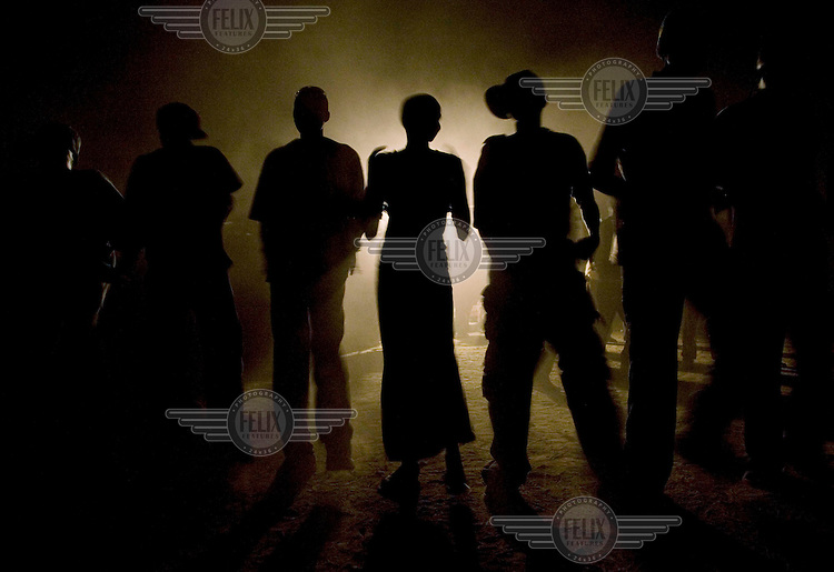 Young men and women dance through the night to a local band during the Twic Olympics in Wunrok, Southern Sudan.