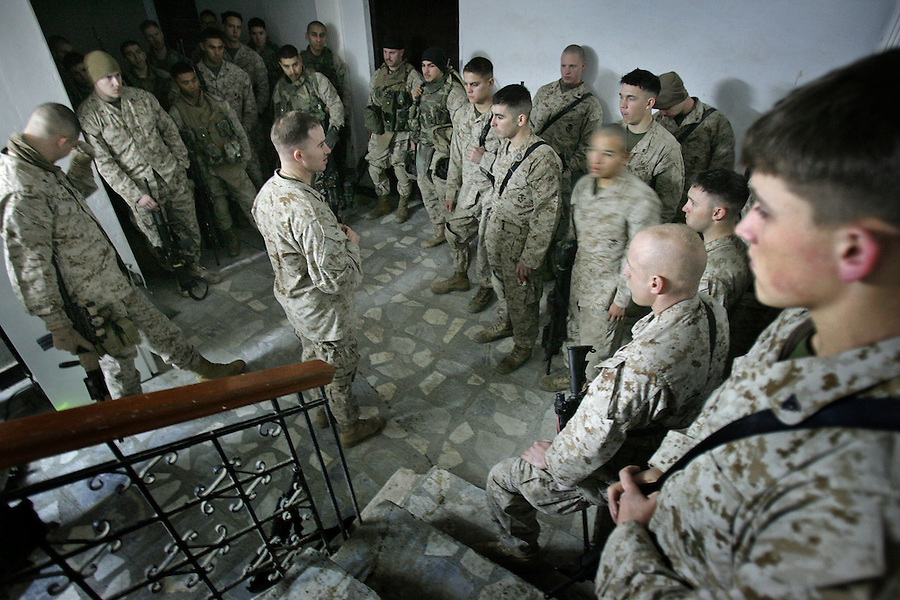 Marines with 2nd Platoon Golf Company 2nd Battalion 5th get the word on the condition of a comrade seriously injured by an RPG during a patrol earlier in the day from their platoon sergeant as they wait to carry out a nighttime raid on a suspected insurgent propagandist's home on January 11, 2005 in Ramadi, Iraq. The raid netted computers, DVDs, and other materials but the target was not apprehended.