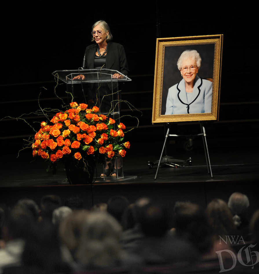 NWA Democrat-Gazette/ANDY SHUPE<br /> Alice Walton, daughter of Wal-Mart founder Sam Walton and a longtime friend of local philanthropist Pat Walker, speaks Thursday, Sept. 8, 2016, beside a photograph of Walker during a public memorial service for Walker at the Springdale High School Performing Arts Center in Springdale. Walker, who helped found the Willard and Pat Walker Charitable Foundation in 1986, died Sept. 2 at the age of 97.