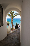 Alleyway leading to blue Mediterranean Sea in the popular holiday resort town of Nerja, Malaga province, Spain
