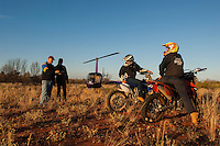 Camel catchers using motor bikes and helicopters preparing for the day, Central Australia, Northern Territory, Australia.