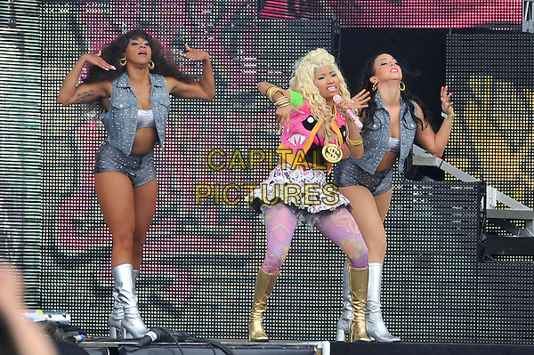 Nicki Minaj.performing at the Barclaycard Wireless Festival, Hyde Park, London, England. 7th July 2012..music live gig on stage show full length live on stage pink tights gold dollar sign necklace  gold knee high boots print patterned white mini skirt  black crop bra top  fur jacket gilet tulle microphone dancing dancers singing .CAP/MAR.© Martin Harris/Capital Pictures.