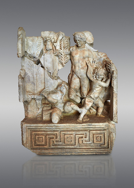 Roman Sebasteion relief  sculpture of Agon Aphrodisias Museum, Aphrodisias, Turkey. <br /> <br /> The scene is an allegory of the athletic contest (or agon). The pillar was a beareded head of Hermes the god of the Gymnasium. Nearby is a palm of victory and a prize table with victory ribbon on it. Two winged baby Eros figures are struggling over a palm branch ( mostly broken): they act out the idea of contest, which is personified in the youthful figure behind. He hold another palm of victory: he is Agon himself.