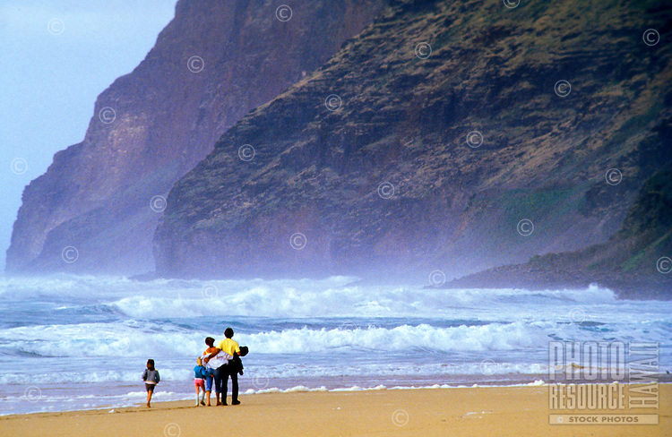 Family walking down pristine Polihale Beach, at the far west end of Kauai