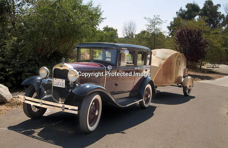 1930 burgundy Ford Model A Town Sedan towing a wood paneled Chummy vintage travel trailer.