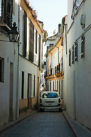 Car driving in a narrow cobbled alley, Cordoba, Andalusia, Spain.