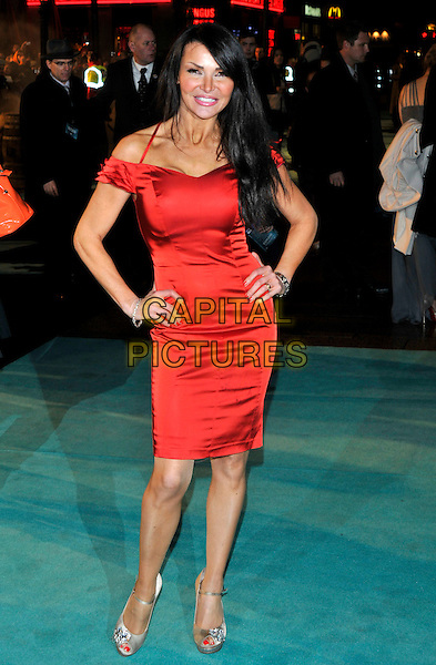 "LIZZIE CUNDY .Attending the World Premiere of ""Sherlock Holmes"", Empire cinema Leicester Square, London, England, UK, .December 14th 2009..arrivals full length red dress hands on hips silk satin off the shoulder silver jewelled peep toe beige shoes ankle strap .CAP/PL.©Phil Loftus/Capital Pictures."