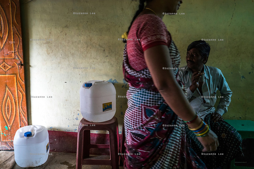 Lavanya Gattu walks past a customer in her food stall in Peddapur, a remote village in Warangal, Telangana, India, on 22nd March 2015. Lavanya buys iJal water and uses it for all her family consumption, and also cooks with it in her stall and serves it for free to customers who come to eat there. She leaves the iJal water cans at the door, showing off to her customers that she uses safe water. Photo by Suzanne Lee/Panos Pictures for Safe Water Network