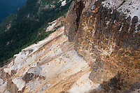When Iodake erupted, the side of the mountain was blown away, leaving a sulphur-yellow cliff that falls away towards Honzawa, Yatsugatake, Nagano, Japan.