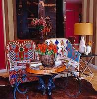A pair of brightly coloured beaded African chairs in the living room