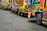 Tap-tap buses pass through the downtown of Port-au-Prince, Haiti, 24 July 2008. Tap-tap vehicles serve as public transportation in Haiti. They are private, operate over fixed routes, departing only when full. Tap-taps are decorated with bright and shiny colors and with a lot of fancy designed elements. There are scenes from the Bible, Christian slogans, TV stars or famous football players often painted on a tap-tap body. Tap-tap name comes from sound of taps on the metal bus body signifying a passenger's request to be dropped off.