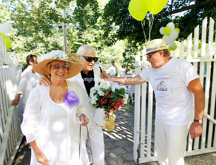"Washington, CT-22 July 2012-072112CM11-  Gael Hammer (right) greets Maura and Frederick Pauli of New Milford at his home during 15th Annual Tea for Two Hundred Saturday afternoon in Washington.  The charity event, hosted by Hammer and Gary Goodwin, raises money for New Milford VNA and Hospice and the Interfaith AIDS Ministry of Greater Danbury.   ""The community is so supportive.  I'm thrilled to have them all."" said co-host Gael Hammer.  He added to-date they've netted approximately 850,000 in donations, since the inception of their charity event.    Christopher Massa Republican-American"