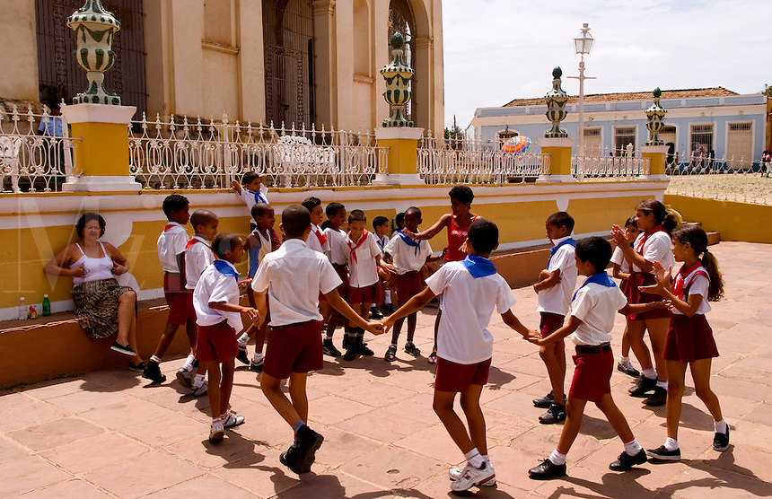 School children playing in circle in town square of the old colonial city of Trinidad in Cuba