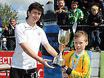 Grove Rangers captain Sam Victory is presented with the winners trophy from Drogheda United's Chris Kerr after his under 10 team beat Grove Rangers at the Drogheda and District schoolboys cup finals in Hunky Dorys park. Photo: Colin Bell/pressphotos.ie