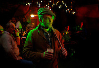 """Matthew Murray, from Co. Meath, waits to perform karaoke in a nightclub.<br /> <br /> The Culchie Festival takes place annually in the town of Athboy, Co. Meath. The festival embraces the stereotypes of the Ireland's rural farmers, and provides an excuse for participants to run amok drinking and carousing through mock contests, as well as nearby towns, farms, pubs, and even wedding parties. The derogatory term """"culchie,"""" similar to """"redneck,"""" is used by natives of urban areas, especially Dublin, to describe people from outside the city. The word is reported to stem from the phrase """"culturally retarded"""" or from those that studied """"agriculture."""""""