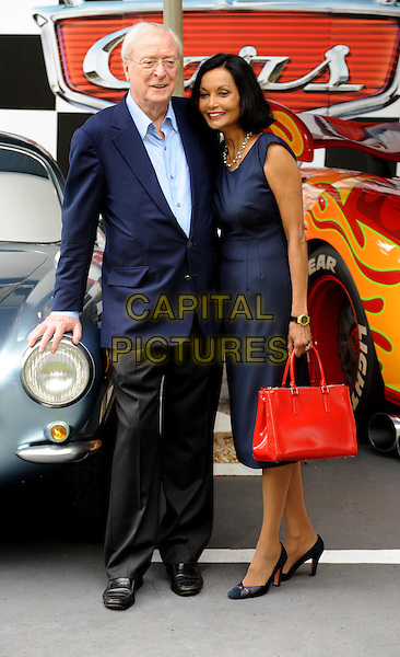Sir Michael Caine & Shakira Caine.UK Premiere of 'Cars 2' at Whitehall Gardens, London, England..July 17th 2011.full length blue dress glasses shirt suit red bag purse jacket married husband wife.CAP/WIZ.© Wizard/Capital Pictures.