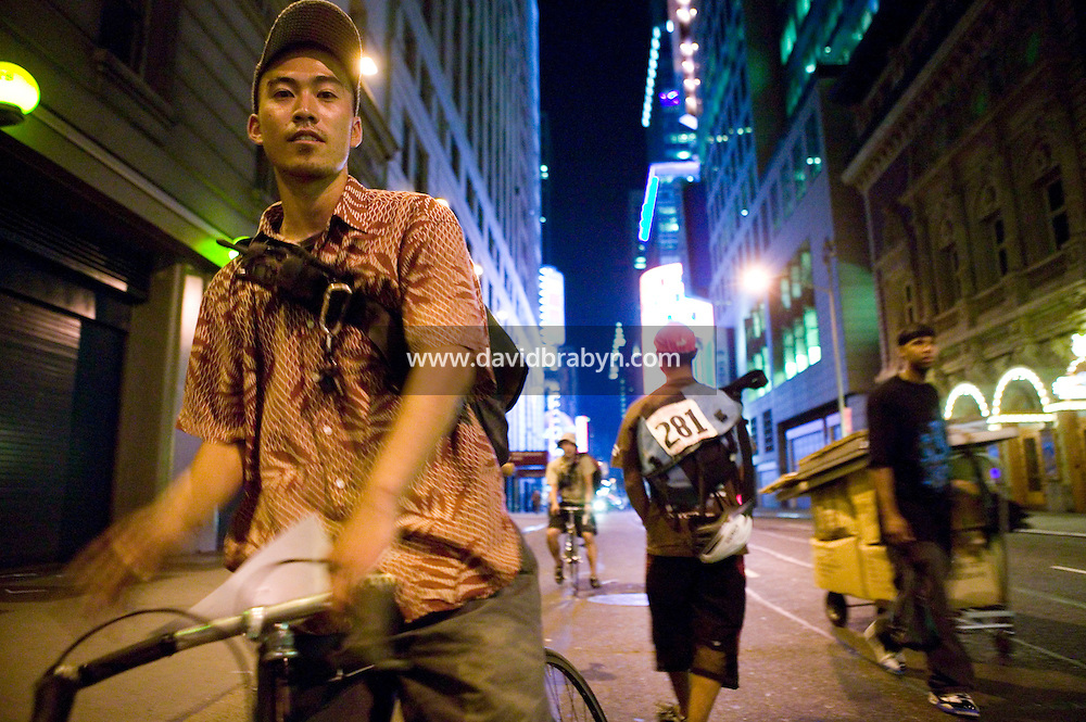 "3 July 2005 - New York City, NY, USA - A rider (L) leaves an alleycat checkpoint manned by ""Junjun"" (2R) on 43rd street in New York City, USA, July 3rd 2005, as another rider (2L) arrives. Alleycats are urban cycle races held informally - without notification of the authorities - on open roads and in real traffic, to simulate the messenger's working conditions. Photo Credit: David Brabyn<br />"