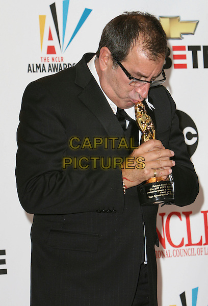 KENNY ORTEGA .2007 NCLR ALMA Awards - Press Room held at the Pasadena Civic Center, Pasadena, California, USA..June 1st, 2007.half length black award trophy glasses suit jacket kiss kissing head down .CAP/ADM/CH.©Charles Harris/AdMedia/Capital Pictures *** Local Caption *** .
