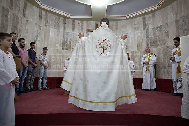 An Iraqi Christian priest delivers mass to Iraqi Christians, many of them recent refugees from Mosul, at a church in Hamdaniyah, Iraq.