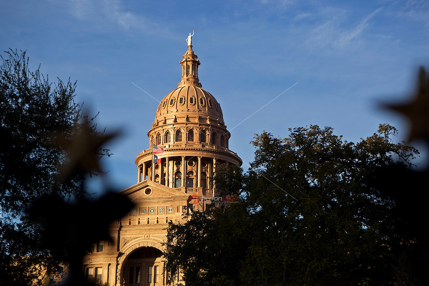 """Texas State Capitol behind the """"Lone Star"""" decorated gates which surround the Capitol Grounds in Austin, Texas, USA."""
