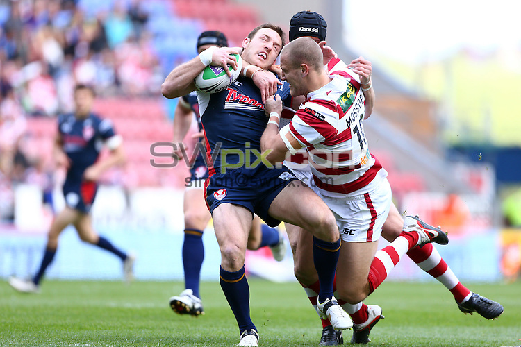 PICTURE BY VAUGHN RIDLEY/SWPIX.COM - Rugby League - Challenge Cup Quarter-Finals - Wigan Warriors v St Helens Saints - DW Stadium, Wigan, England - 12/05/12 - St Helens James Roby is tackled by Wigan's Lee Mossop and Paul Prescott.