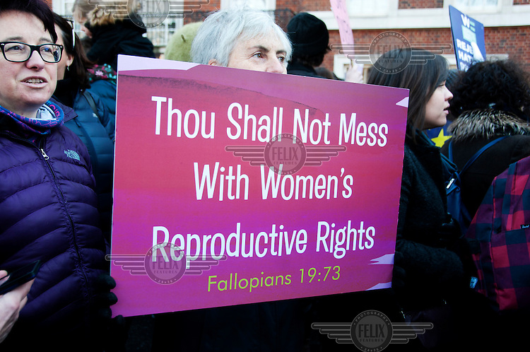 A woman holds a placard that reads: 'Thou shalt not mess with women's reproductive rights. Fallopians 19:73'.<br /> <br /> <br /> An estimated 100,000 protesters took part in a Women's March from the US Embassy in Grosvenor Square to Trafalgar Square as part of an international campaign on the first full day of Donald Trump's Presidency of the United States.