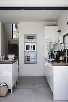 The kitchen is handmade and designed by Dita Living, while the stainless steel appliances are all Gaggenau. Rather than disrupt such an elegantly minimalist space with a cooker hood, a downdraft extractor rises up from the worktop when required.