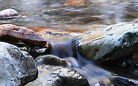 Soft blur makes this scene of a forest creek look ever so serene. Water flows softly between huge boulders as it makes it's way into Lake Koocanusa in Montana.