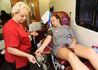 NWA Democrat-Gazette/ANDY SHUPE<br /> Kathryn Revelle, (right) a freshman at the University of Arkansas from Austin, Texas, is assisted Wednesday, Sept. 9, 2015, by Paula Coffman, a donor specialist for the Community Blood Center of the Ozarks, while donating blood during the annual Muslims for Life blood drive sponsored by Al-Islam Students Association at the University of Arkansas in Fayetteville. The event marks the 14th anniversary of the 9/11 terrorist attacks and had the goal of collecting 200 pints of blood from the campus community.