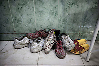 In this Thursday, Nov. 01, 2012 photo, a pile of shoes covered by blood from wounded or dead residents is viewed at the entrance of the emergency ward at one hospital in the nearby Tarik Al-Bab neighborhood in Aleppo, the Syrian's largest city. (AP Photo/Narciso Contreras).