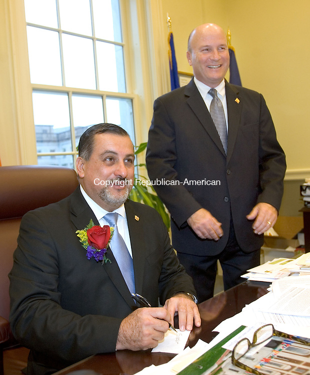 WATERBURY CT. 09 August 2013-080913SV04-Ra&uacute;l A. Erazo Velarde of New Haven sits at the mayor&rsquo;s desk with chief of staff Joe Geary at his side in Waterbury Friday. Velarde was named Ecuadorian Mayor for the Day in Waterbury. Consul General Erazo was born in Guayaquil, Ecuador in 1963.<br /> Steven Valenti Republican-American