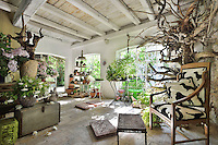 A rustic garden room with a beamed ceiling and tiled floor. Potted plants and terracotta pots are arranged around the room. A wooden chair stands in one corner.