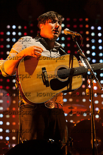 MUMFORD & SONS - vocalist Marcus Mumford on acoustic guitar - performing live at the O2 Arena in London UK - 11 Dec 2012.  Photo credit: John Rahim/Music Pics/IconicPix