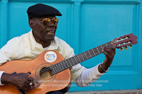 TH40211-D. A man playing the guitar in Old Havana (Habana Vieja in Spanish). Havana, Cuba.<br /> Photo Copyright &copy; Brandon Cole. All rights reserved worldwide.  www.brandoncole.com