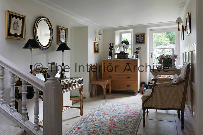 A stone flagged hallway furnished with antique illustrations on the walls and a variety of furniture
