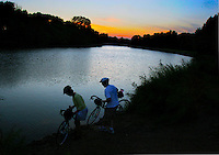 Beneath the dusk's final glow, Darla and Craig Bruggeman of Inwood dip their tires into the Rock River Saturday evening the night before the outset of RAGBRAI XXXV in Rock Rapids.  It is the first RAGBRAI for the couple, who choose to train for and join the ride this year because it started in their home county.