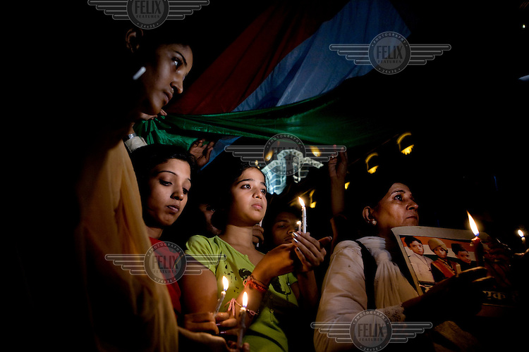 People light candles outside the Taj Mahal Palace hotel on the first anniversary of the Mumbai 26/11 terrorist attacks.