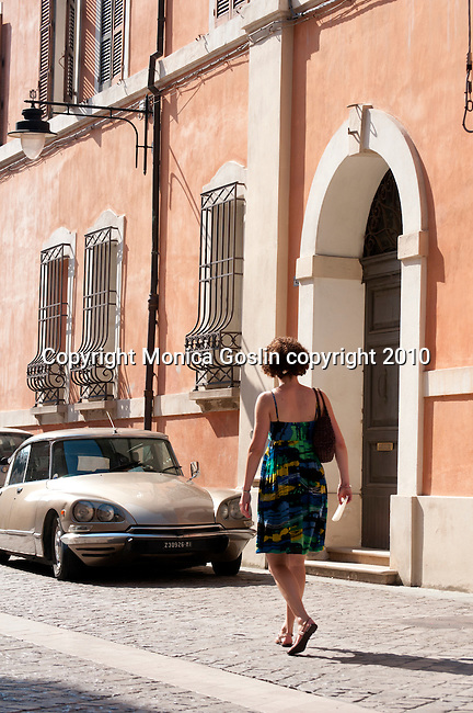 A woman in a sun dress walks down a street in Ravenna, Italy.