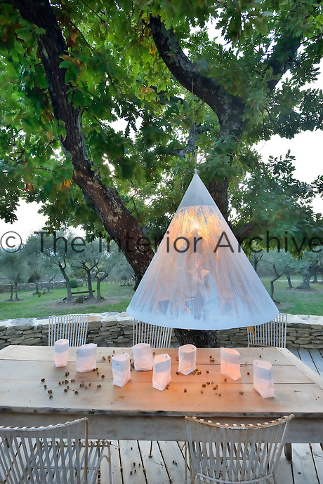 An illuminated artwork by José Esteves is suspended from the oak tree overlooking this outdoor dining area, the table decorated with illuminated bags by Le Repère des Belettes