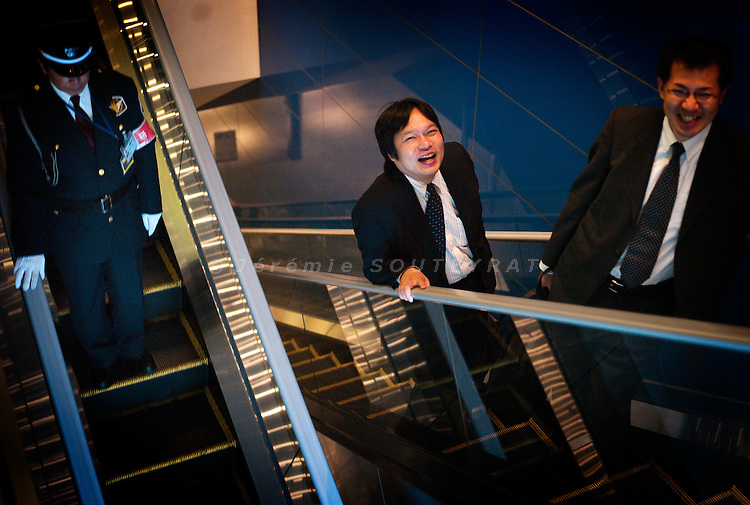 Tokyo - 23rd of October 2009 - Two salarymen laughing on the escalator of a commercial center