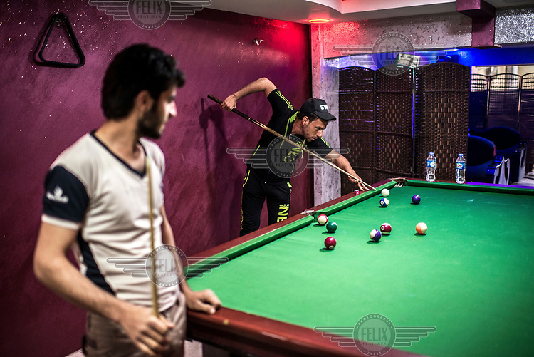 Young men play nine ball in a pool hall in eastern Mosul, which was retaken from ISIS militants in late 2016.