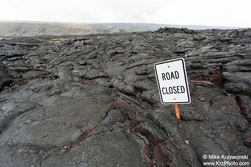 """""""Road Closed"""" sign emerging out of a lava covered road in the Hawaii Volcanoes National Park, Big Island"""