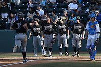 John Schuknecht #2, Nick Torres #10, Jordan Ellis #26, Jimmy Allen #15 of the Cal Poly Mustangs prepare to greet teammate Brian Mundell #16 after his home run against the UCLA Bruins at Jackie Robinson Stadium on February 22, 2014 in Los Angeles, California. Cal Poly defeated UCLA, 8-0. (Larry Goren/Four Seam Images)
