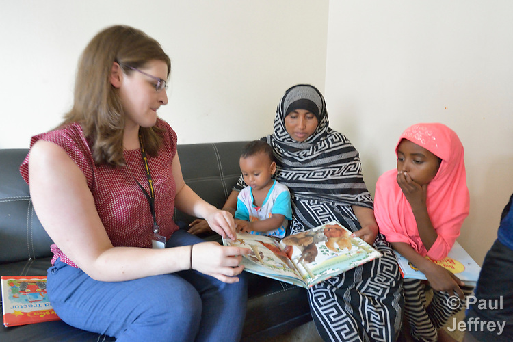 Christine Baer, a congregational resource developer with Church World Service in Lancaster, Pennsylvania, helps Mekiya Kebir and her children Hashim and Aysha read a book as she delivers a backpack full of books and art supplies to the recently arrived Eritrean refugee family. Church World Service resettles refugees in Pennsylvania and other locations in the United States. <br /> <br /> Photo by Paul Jeffrey for Church World Service.
