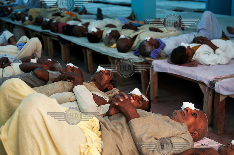 Men lie in the post operative ward at Akhand Jyoti Eye Hospital in Mastichak.