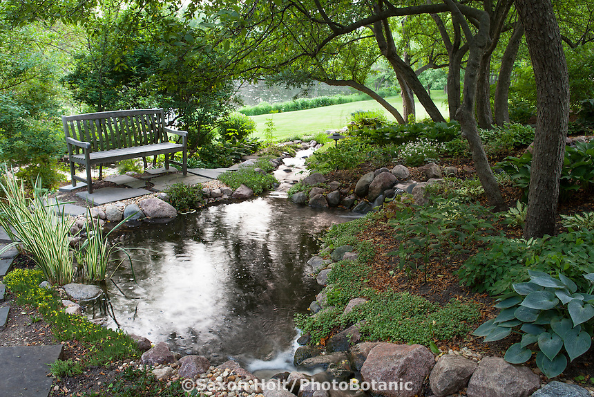 Bench by stepping stone path and tranquil stream, water feature in shady garden