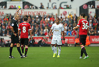 Pictured: Match referee Martin Atkinson shows a yellow card to Wayne Routledge of Swansea (C) Sunday 30 August 2015<br /> Re: Premier League, Swansea v Manchester United at the Liberty Stadium, Swansea, UK