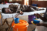Sylvester, 16, looks up from his bed while a nurse prepares a fortified porridge for him to eat at Wellington Cholera Treatment Center, Freetown, Sierra Leone, Aug. 14, 2012. Médecins Sans Frontières Belgium, in collaboration with the Sierra Leone Ministry of Health, is running four emergency cholera treatment centers to keep up with the number of patients. Many of the roughly 120 daily patients seen by the MSF team come from extremely impoverished areas of the densely-populated capital, where proper systems for drainage and waste disposal are almost non-existent. Outbreaks of water-borne diseases like cholera become even more likely during the rainy season, which is expected to last at least two more months.
