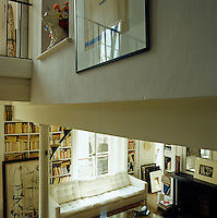 View from the staircase down to a white Knoll sofa in the cluttered library
