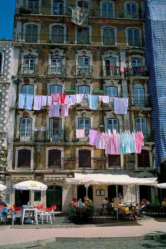 Portugal, Lisbon. Residential hotel with laundry hanging from balconies and sidewalk cafe. Lisbon, Portugal.